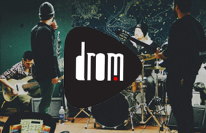 drom logo in front of a band practing