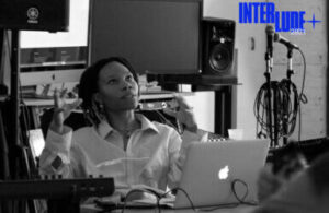 Interlude + 2021 Person sitting at laptop in recording studio